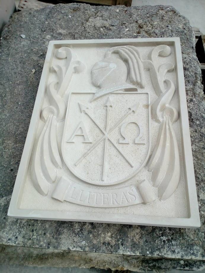 escudo de piedra con yelmo y lambrequines