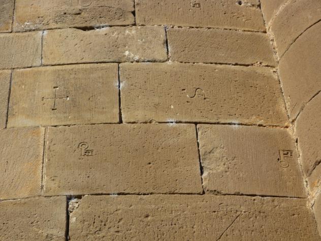 marcas de cantero en los sillares de un muro de piedra
