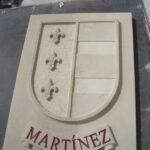 escudos heráldicos en piedra con cinta y apellido
